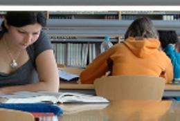 Mujer estudiando a la mesa en una biblioteca con varios libros. Al fondo, más estudiantes.