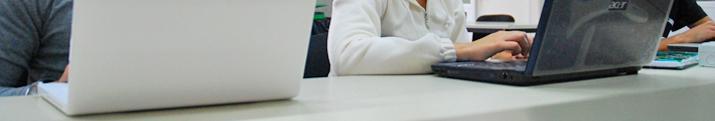 Detalle de tres alumnos consultando información mediante portátiles