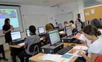 Vista del interior de un aula con alumnado siguiendo un curso con ordenadores