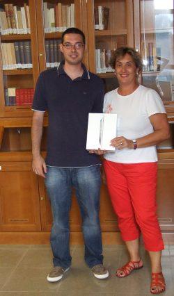 La directora de la Biblioteca Universitaria, sosteniendo la tableta, y el ganador del concurso posan sonrientes frente a unas vitrinas de la Biblioteca Musicológica Lothar Siemens