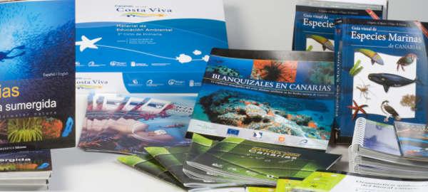 Fotografía de diversas publicaciones de Oceanográfica, fundamentalmente libros y folletos, algunos de pie y otros tendidos. Las cubiertas reproducen imágnes de fondos marinos coloridos.