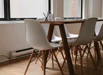 Vista de una sala con una mesa con sillas de reunión